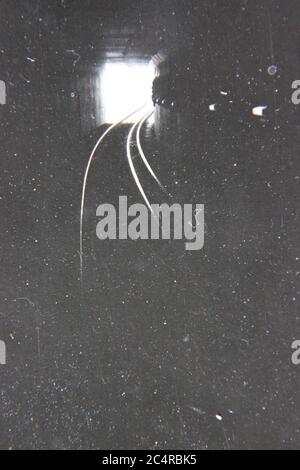 Fotografía en blanco y negro de la época de los 70 de las pistas de tren que conducen a la luz al final del túnel. Foto de stock