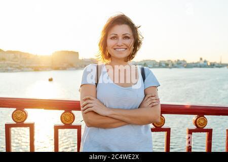 Estilo de vida retrato al aire libre de mujer sonriente madura con brazos doblados