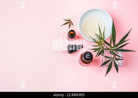 Ramita de cáñamo en un jarrón de vidrio, botellas de aceite de cannabis y una taza con aceite sobre fondo rosa