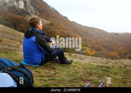 Joven excursionista turístico con mochila sentado y relajarse en la cima de la colina en las montañas y mirando al hermoso paisaje de otoño amarillo puesta de sol
