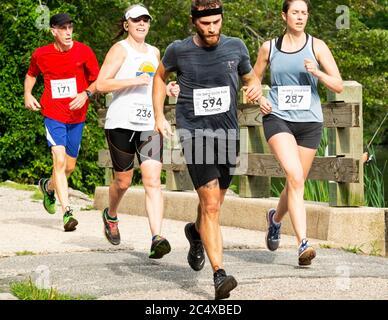 Babylon, Nueva York, EE.UU. - 12 de agosto de 2018: Un grupo de corredores que corren el Dirty Sock 10K en una mañana de verano caliente mientras cruzan el puente de pesca en Sou
