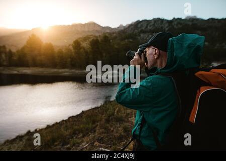 Hombre mayor en vacaciones de senderismo tomando fotografías de hermosa vista con una cámara digital. Hombre mayor de pie junto al río en el bosque y haciendo fotos.