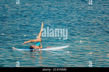 Mujer joven en baño azul haciendo yoga en sup. con pala. Postura equilibrada - concepto de vida sana y equilibrio natural entre el cuerpo y el mental