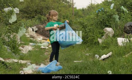 Niña voluntaria niña niña niña en camiseta verde que titilan la basura en el parque, limpiando el bosque sucio de bolsas de plástico, botellas. Recoger basura. Recicle. Reducir la contaminación por celofán ambiental. Salvar la naturaleza