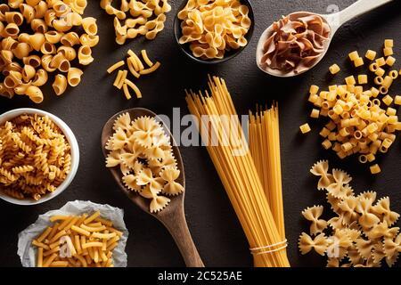 Montón de varias pastas crudas en diferentes tipos y formas sobre fondo marrón oscuro. Vista de gastos generales.