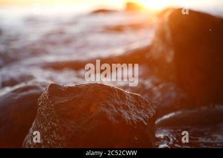 Piedras de playa y piedras de Stony puestas de sol en el cierre de la tarde, textura puesta de sol y amanecer