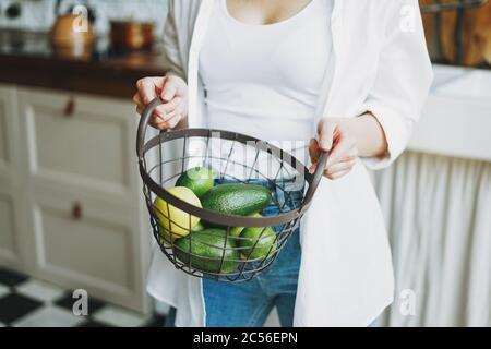 Foto de la cosecha de la mujer joven en camisa blanca sostenga la cesta con frutas y verduras verdes en la cocina Foto de stock