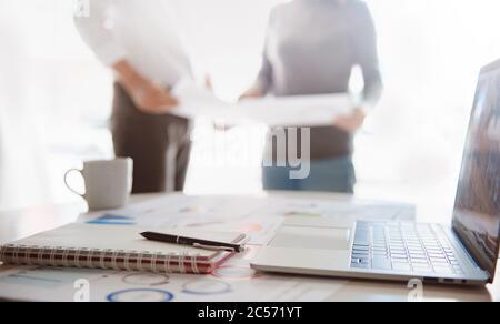 Blur Cerrar un bolígrafo y un ordenador mostrando datos financieros, grupo de negocios en segundo plano