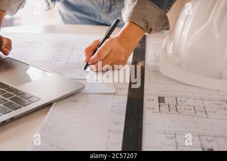 Ingenieros que sostienen un bolígrafo que apunta a un edificio y el diseño de plan de construcción de la estructura como guía para los constructores con detalles.Ingeniería y construcción co