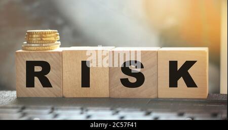 Palabra de riesgo sobre bloques de madera dispuestos detrás del teclado de la computadora y la pila de monedas. Concepto de negocio de inversión arriesgado