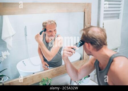 Hombre sonriente haciendo un corte de pelo de nuevo estilo recortando un pelo con un barbero eléctrico recargable mirando en el espejo del baño. Peinado, cuidado del cuerpo y de la piel