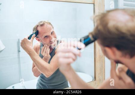 Concepto de tratamiento corporal y de cuidado de la piel. Hombre sonriente haciendo un corte de pelo de nuevo estilo recortando un pelo usando un barbero eléctrico recargable mirando en el cuarto de baño