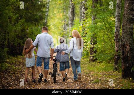 Feliz familia al aire libre sonriendo en un bosque de verano