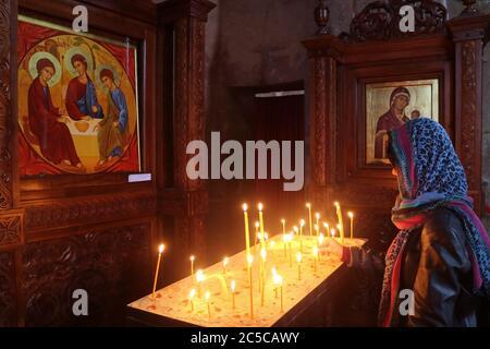 Mujer ofreciendo una vela en la histórica Iglesia del Monasterio de Jvari, Mtskheta, la antigua capital de Georgia Foto de stock