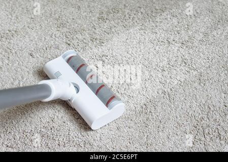 Cabezal de aspiradora en alfombra sucia con tira limpia. Tareas domésticas con el uso de hoover. Cepillo Turbo de primer plano de aspirador moderno. Limpieza del hogar y ca