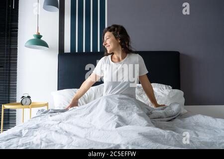 Hermosa chica despierta en un buen estado de ánimo en un apartamento con estilo. Se estira con una sonrisa comenzando el día.