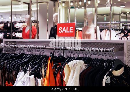 Venta de letrero en tienda de ropa. Ventana borrosa mojada sobre fondo