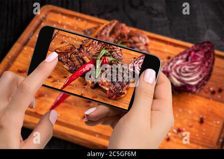 Fotografiar el concepto de comida - turista toma una foto de la carne de ternera lista para comer en el cortando tabla de madera en el smartphone.