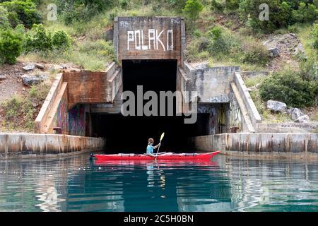 Mujer kayak en ex Yugoslavia submarino secreto salida de la base de montaña, península de Lustica, Montenegro Foto de stock