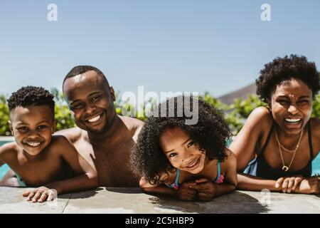 Feliz familia joven en la piscina en un día de verano. Familia de cuatro disfrutando de sus vacaciones de verano.