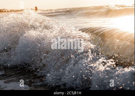 Olas en el océano salpicando olas. Sol