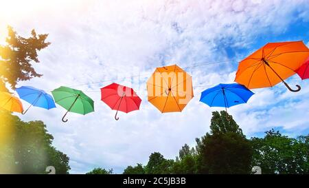 Paraguas de fondo de colores. Brillantes sombrillas multicolores en el cielo. Decoración de calle con sombrillas.
