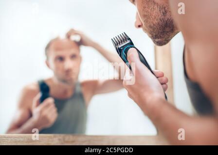 Hombre mirando el espejo del baño y pensando en su nuevo estilo de corte de pelo analizando pelos.eléctrico recargable Trimmer cerrar enfoque imagen. De radical