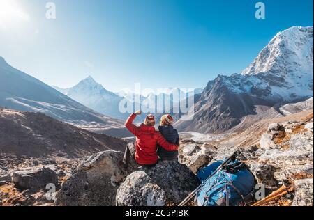 Pareja joven regocijándose en Everest base Camp ruta de senderismo cerca de Dughla 4620m. Backpackers izquierda mochilas y bastones de senderismo y disfrutar de la vista del valle w