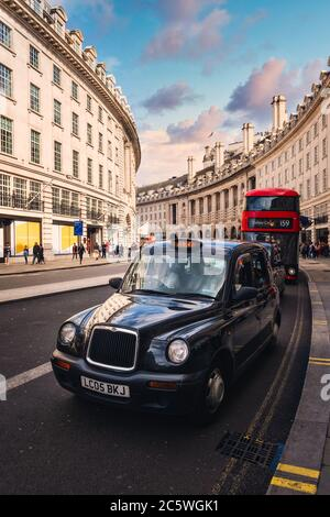 Típico taxi negro y autobús rojo de dos pisos en Regent Street en Londres