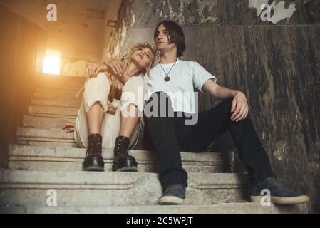 Una joven pareja sentada en un lugar arruinado Foto de stock