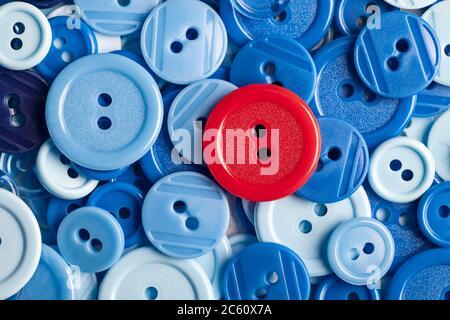 Botón rojo sobre fondo de botones de plástico azul. Este archivo se limpia y se vuelve a archivar.