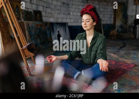 Joven hermosa mujer con los ojos de cierre sentado en la estera de yoga en la pose de loto y meditando mientras pasa tiempo en un acogedor taller
