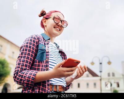 Sonriente hermosa joven joven adolescente Retrato con extraordinario peinado en camisa de cuadros sosteniendo un delgado smartphone en la mano. Adolescente moderno