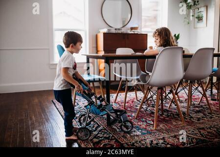 Hermano joven mostrando a un animal de peluche en cochecito a la hermana inicio