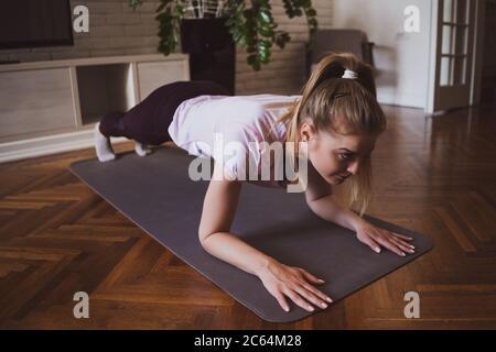 Mujer joven practicando pilates y ejercicios de yoga en casa. Ella está haciendo flexiones.