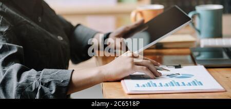 Análisis de la mujer de negocios informe financiero con tablet ordenador.