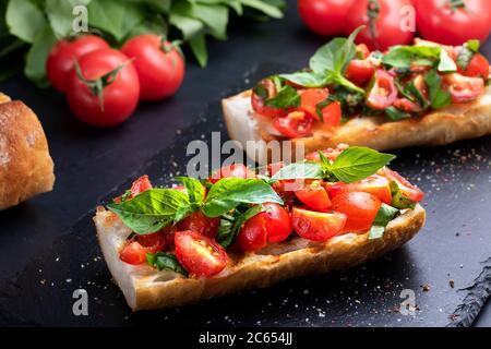 Bruschetta casera con tomates cherry y albahaca primer plano en una pizarra. Cocina italiana. Antipasti. Comida vegetariana Foto de stock