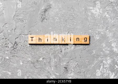 pensar palabra escrita en bloque de madera. pensar texto en tabla de cemento para su diseño, concepto.