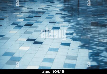 Una superficie de suelo de baldosas de una piscina de la calle con agua de color azul clásico, con algunas baldosas de un tono diferente y una sombra diagonal a la derecha