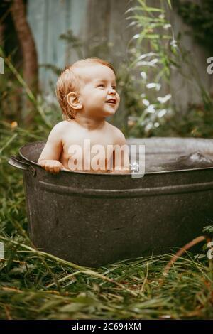 Lindo gracioso chico baño en tina galvanizado al aire libre en un jardín verde.