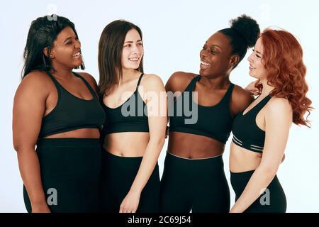 Grupo de mujeres de diferentes razas, figuras y tamaños en ropa deportiva de pie juntos, charlando y riendo contra fondo blanco.