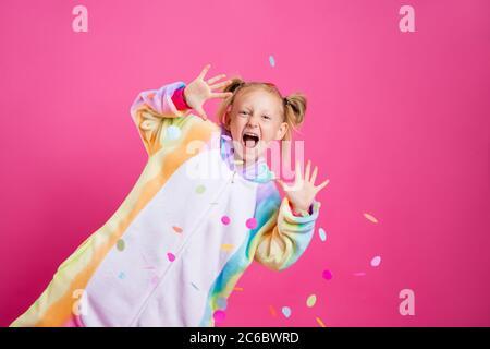 Feliz niña en kigurumi unicorn sobre un fondo rosa se regocija en confeti multicolor, espacio para el texto