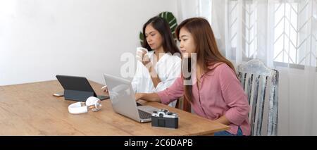Fotografía recortada de estudiantes universitarios que realizan su proyecto con dispositivos digitales y cámara en mesa de madera