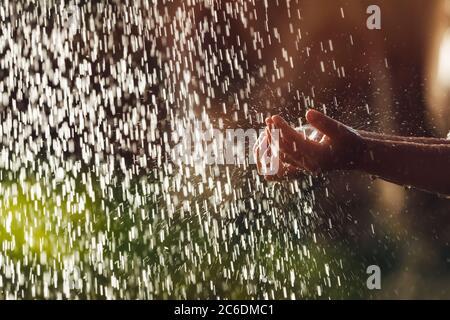 El niño se lava las manos bajo la lluvia de la ducha tropical. Los niños tienen diversión al aire libre en el complejo de la playa. Actividades de verano. Bebé feliz con una infancia saludable
