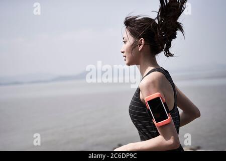 joven mujer adulta asiática corriendo jogging al aire libre junto al mar, vista lateral