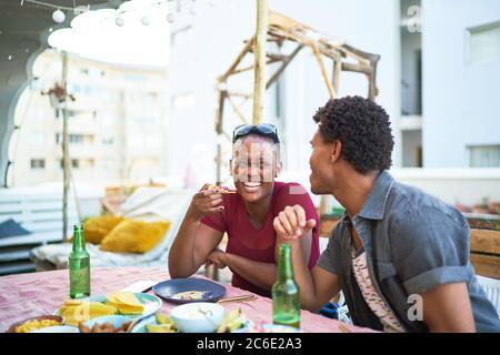 Feliz pareja joven comiendo en la mesa del patio