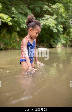 Una niña se desata y salpican en el río Shenandoah, Virginia, EE.UU. Foto de stock