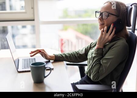 Joven hermosa mujer en gafas hablando en el teléfono móvil y utilizando el portátil con una sonrisa mientras se sienta en su lugar de trabajo