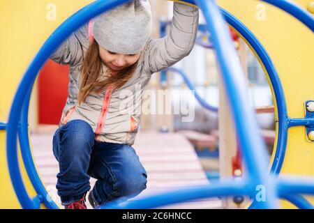 Chica feliz jugando en el patio de juegos