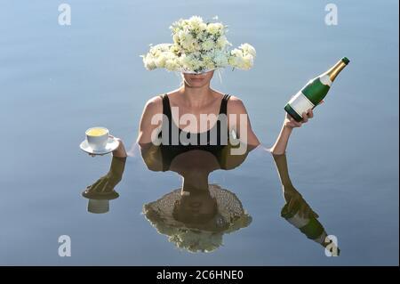 Mujer joven sirviendo una taza de café y champán